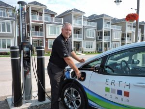 Chris White President and CEO of ERTH Corporation plugging in an electric vehicle charger