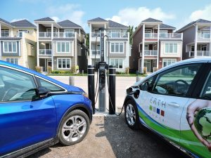 Two electric vehicles plugged into an electric vehicle charging station in Port Stanley