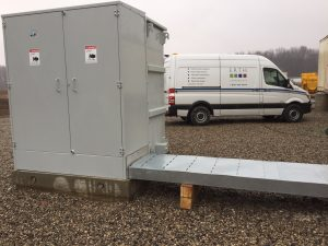 Substation outdoors with ERTH Corporation fleet vehicle parked nearby